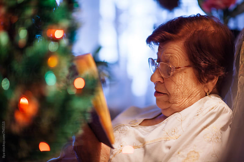 Portrait of old woman reading book near Christmas tree  by Ilya for Stocksy United