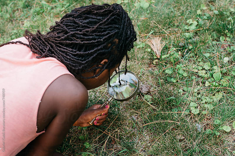 Black girl looking through a magnifying glass by Gabriel (Gabi) Bucataru for Stocksy United