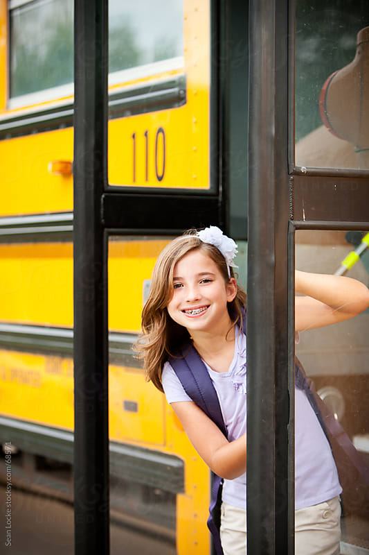 School Bus: Girl Peeks Around Door by Sean Locke for Stocksy United