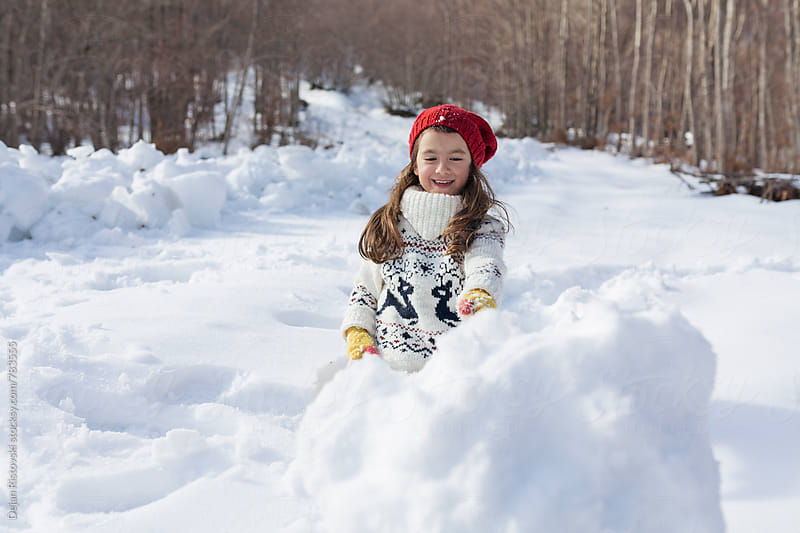 Child rolling a big snowballs. by Dejan Ristovski for Stocksy United