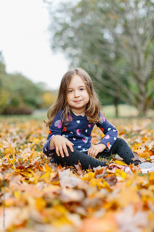 Portrait of a cute girl sitting in bed of leaves by Jakob for Stocksy United