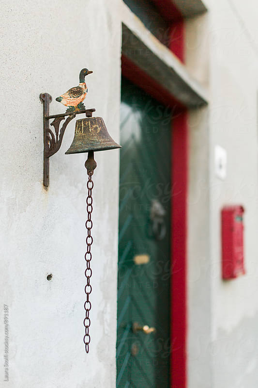 Old iron duck stands on top of bell ring in front of door by Laura Stolfi for Stocksy United