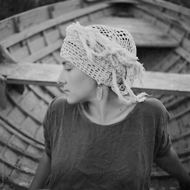 A black and white film portrait of young beautiful woman seating in the boat by Anna Malgina for Stocksy United