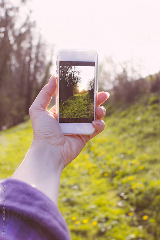 Taking a picture with a smartphone by Milena Milani for Stocksy United