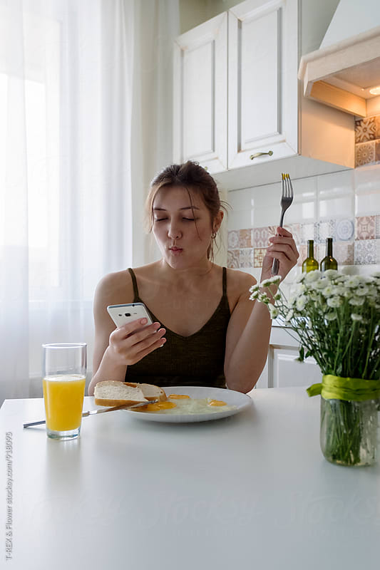 Woman using smartphone while having breakfast by T-REX & Flower for Stocksy United