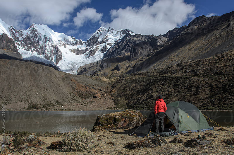 Man in front of tent looking at snow-capped mountains by Mick Follari for Stocksy United