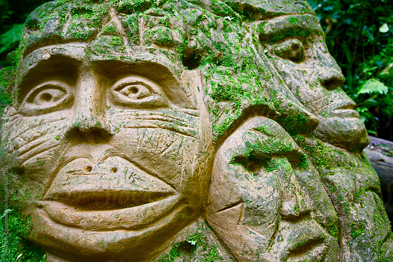 Hand carved tribal faces on rock or clay in the jungle, Banos, Ecuador by Jaydene Chapman for Stocksy United