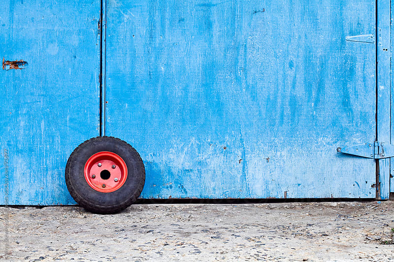 Minimalist image of a red wheel leaning against a blue door by anya brewley schultheiss for Stocksy United