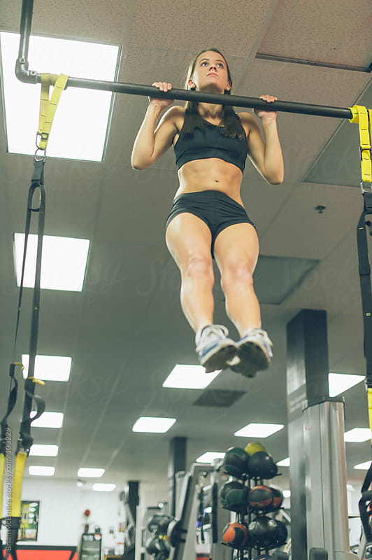 Fit Woman Doing Pull-Ups In Gym by Brian McEntire for Stocksy United