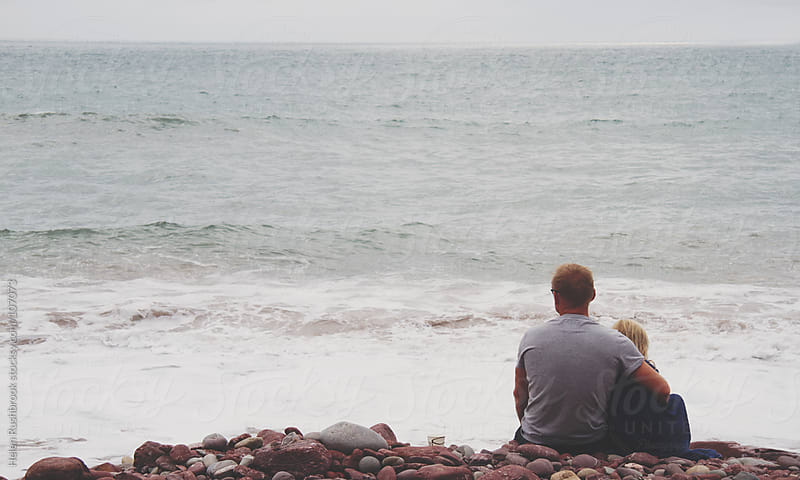 A father and daughter sitting on a beach looking out to sea. by Helen Rushbrook for Stocksy United
