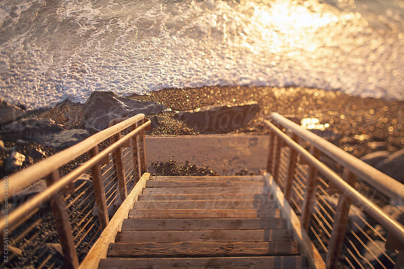 A staircase leading down to a rocky shoreline at sunset. by RZ CREATIVE for Stocksy United