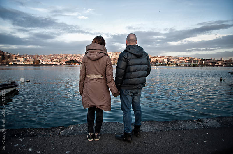 Back view of young couple Holding Hands looking Istanbul landscape on the bosphorus by Jean-Claude Manfredi for Stocksy United