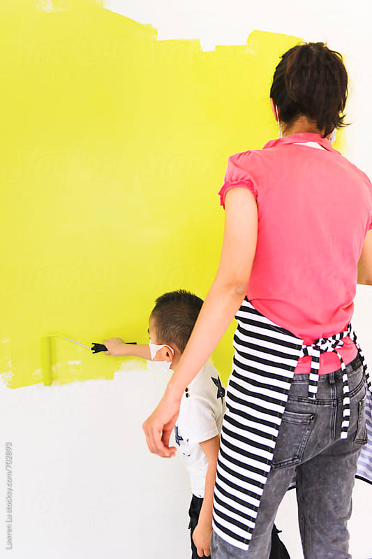 Woman and kid painting their home by rollers by Lawren Lu for Stocksy United