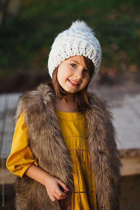 Cute and stylish young girl dressed for fall, looking at camera by Amanda Worrall for Stocksy United