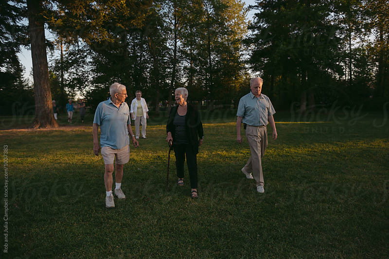 Fun portrait of happy caucasian seniors walking outside in nature by Rob and Julia Campbell for Stocksy United