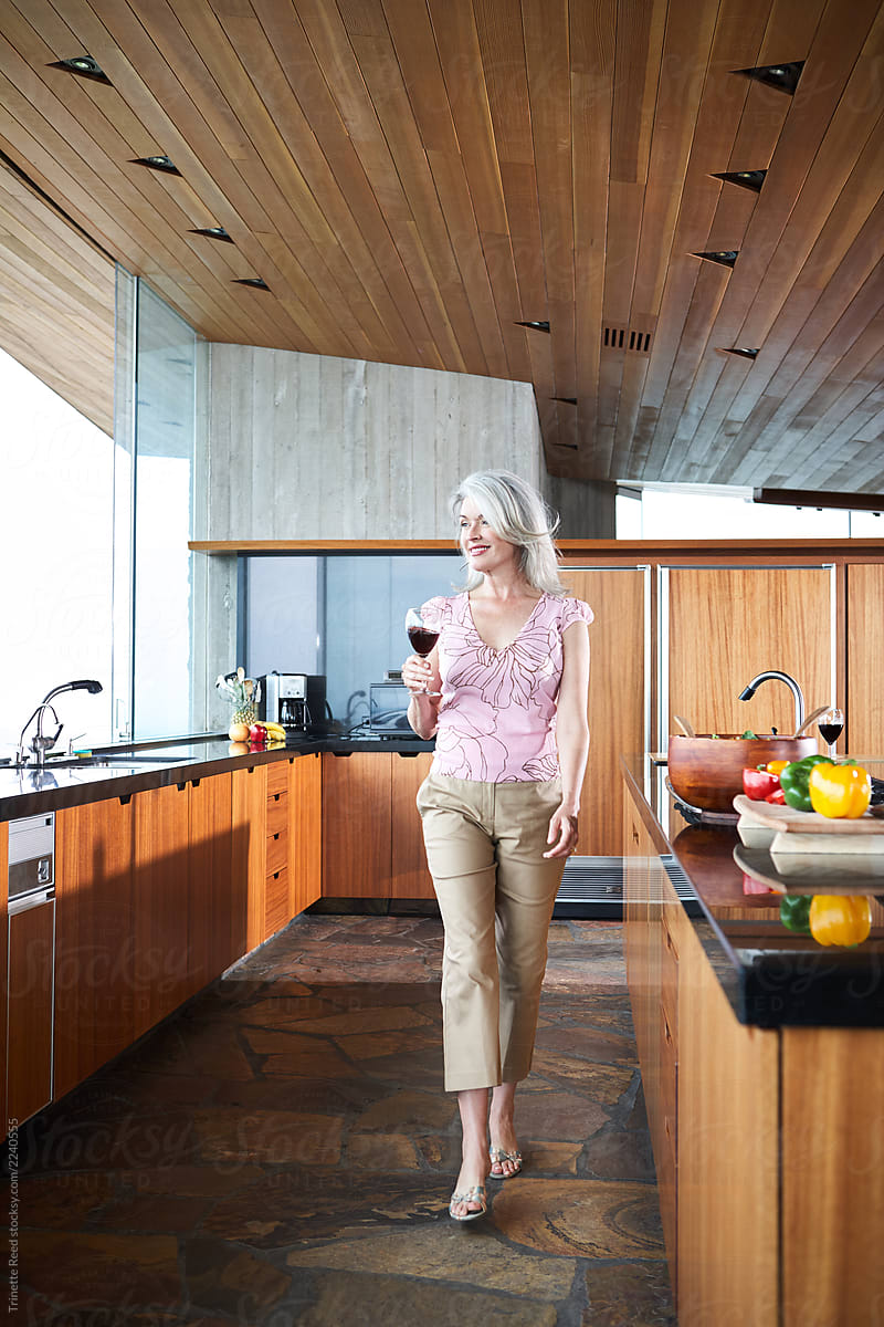 Mature woman with grey hair walking in luxury kitchen by