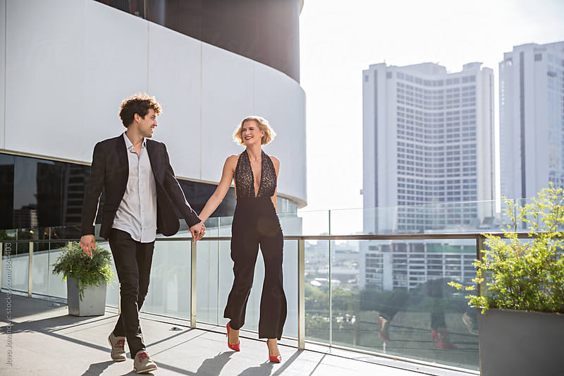 Handsome and stylish young couple holding hands and walking on a city balcony  by Jovo Jovanovic for Stocksy United