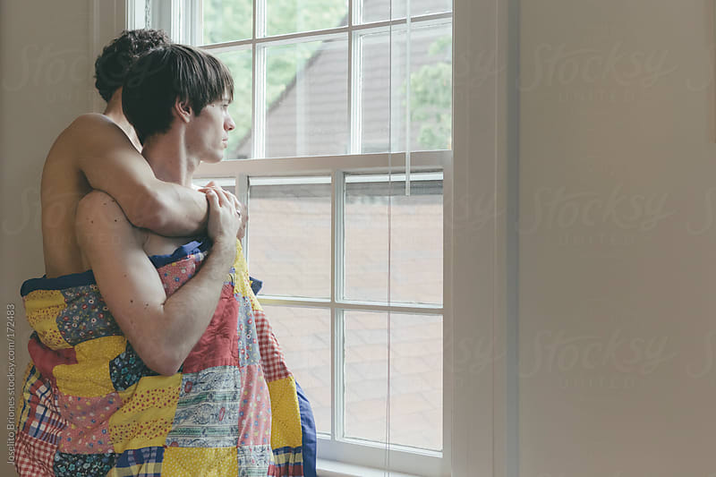 Embracing Gay Men Couple with Blanket Looking Out their Bedroom Window by Joselito Briones for Stocksy United