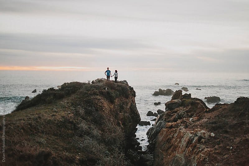 A couple holding hands on a sea cliff by Dylan M Howell Photography for Stocksy United