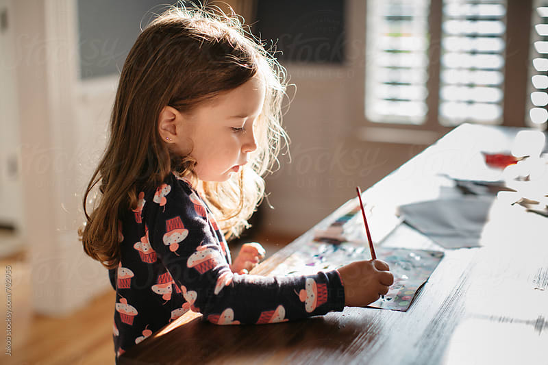 Cute young girl painting watercolors on a dining room table by Jakob for Stocksy United
