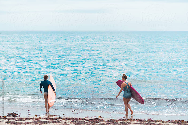 Two Young Women Carrying Surfboards into the Ocean by Briana Morrison for Stocksy United