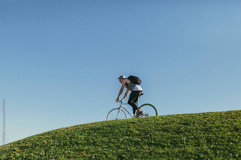 Youn Man Cycling Downhill in a Sunny Day by Victor Torres for Stocksy United