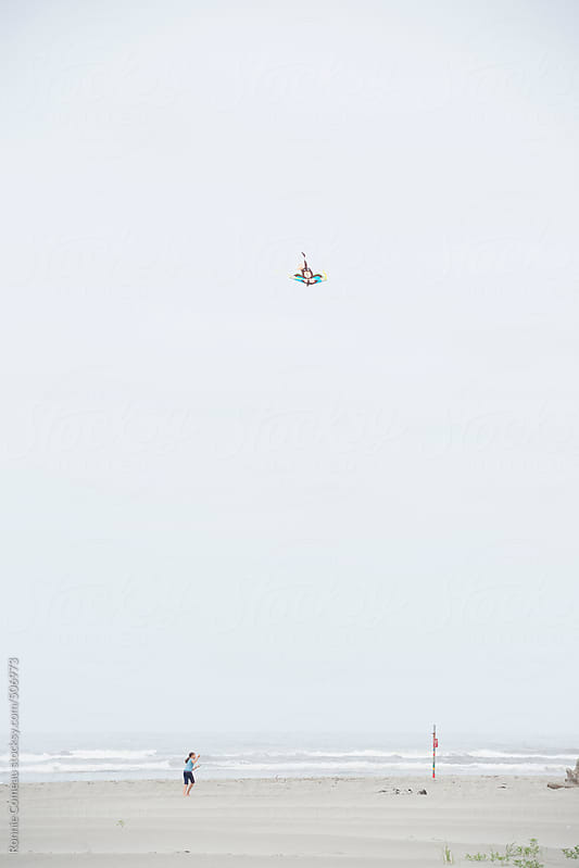 Girl Flying A Kite On The Beach by Ronnie Comeau for Stocksy United