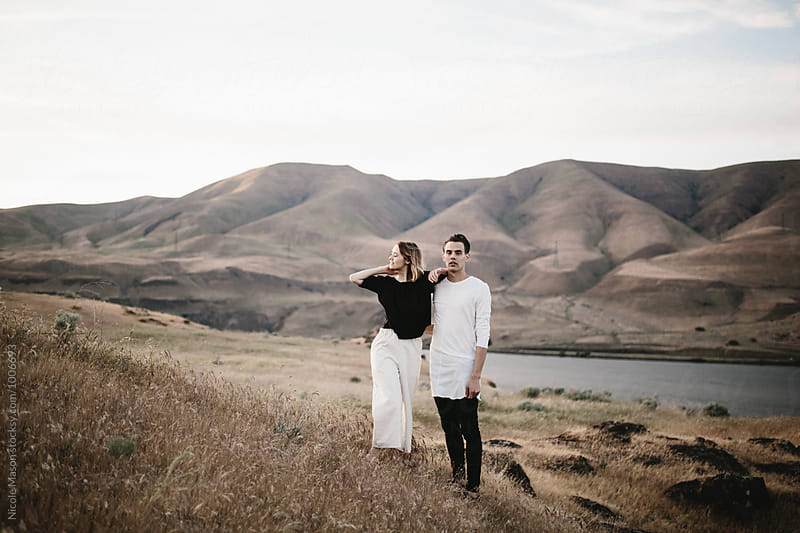 modern fashionable couple standing in desert landscape by Nicole Mason for Stocksy United