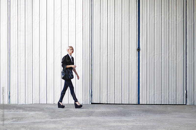 Young businesswoman walking on street by Jovana Rikalo for Stocksy United