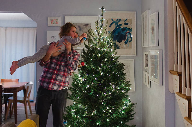 little girls puts ornaments on a Christmas tree with the help of her father by Meaghan Curry for Stocksy United