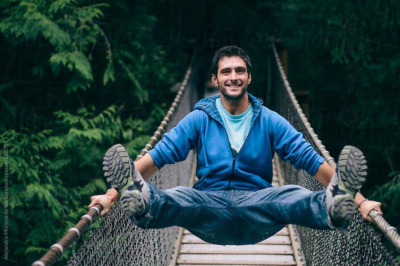 Young man having fun on a suspension bridge by Alejandro Moreno de Carlos for Stocksy United