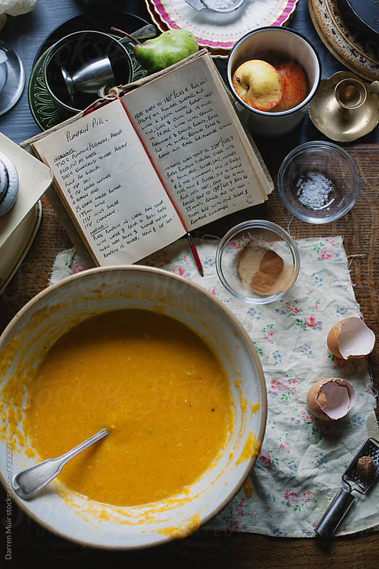 Pumpkin pie filling in a bowl on a table,surrounded by other ingredients and a recipe book by Darren Muir for Stocksy United