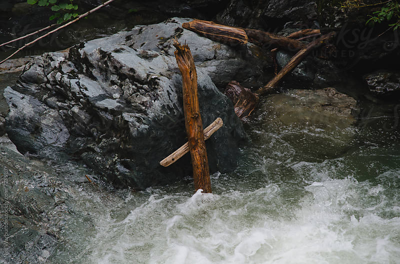 Driftwood in fast flowing river making a cross by Neil Warburton for Stocksy United
