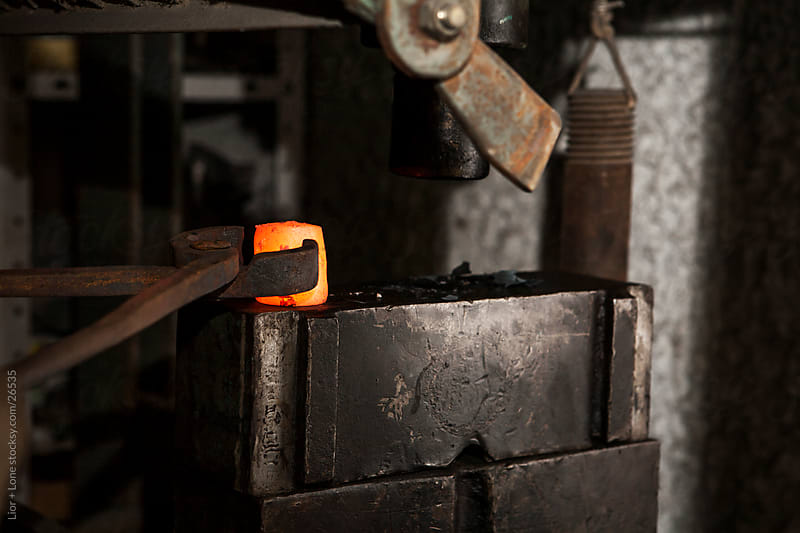 Pliers placing hot metal on anvil by Lior + Lone for Stocksy United
