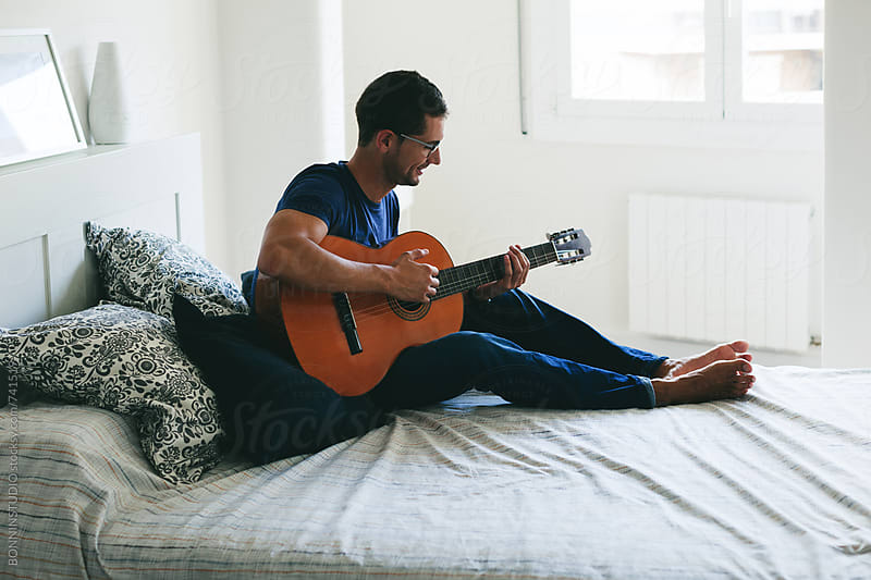 Man playing guitar on his bedroom.  by BONNINSTUDIO for Stocksy United