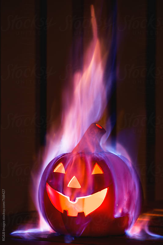 Evil halloween pumpkin burning in a dark room by RG&B Images for Stocksy United