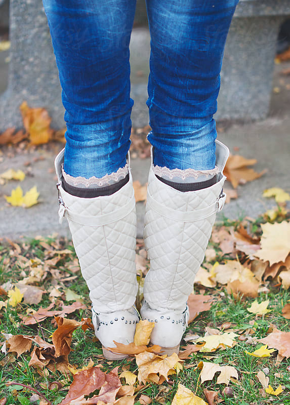 A woman wearing light colored fall boots stands among fall leaves by Tana Teel for Stocksy United