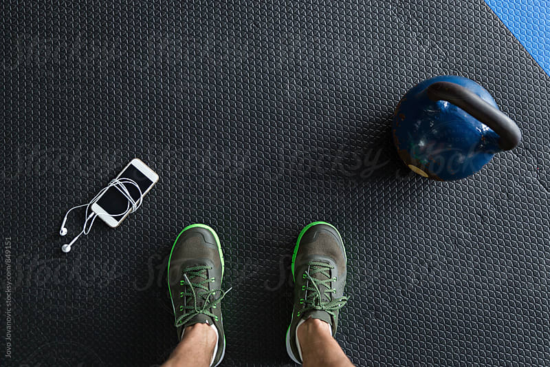 Closeup of feet standing next to a kettlebell and a smartphone on the gym floor  by Jovo Jovanovic for Stocksy United
