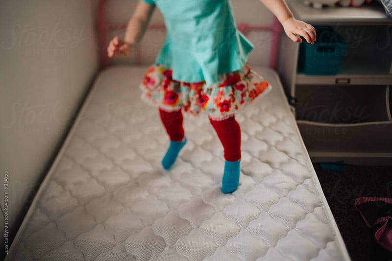 Girl jumping on bed by Jessica Byrum for Stocksy United