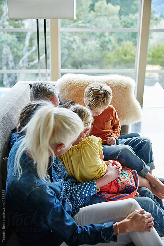 Family having fun together on the sofa in living room by Trinette Reed for Stocksy United