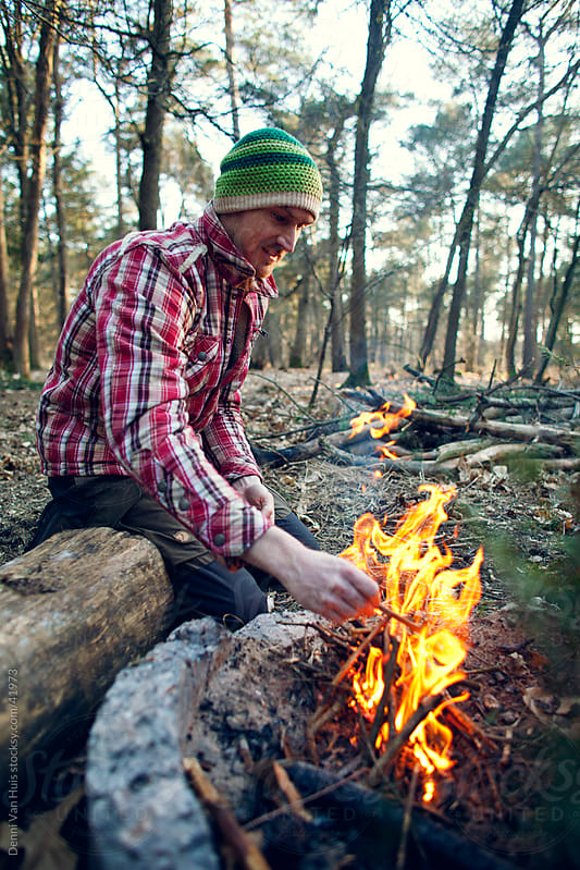 Young man sitting next to a campfire in a forest by Denni Van Huis for Stocksy United