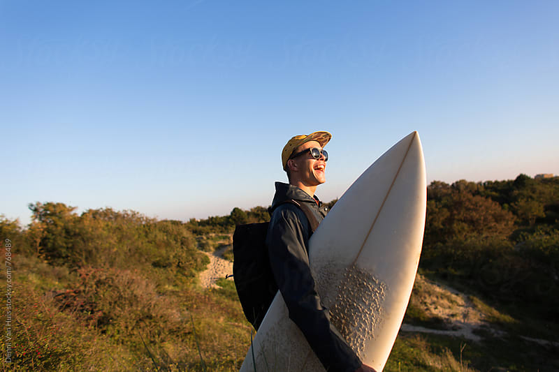 A surfer with his board in the dunes. by Denni Van Huis for Stocksy United