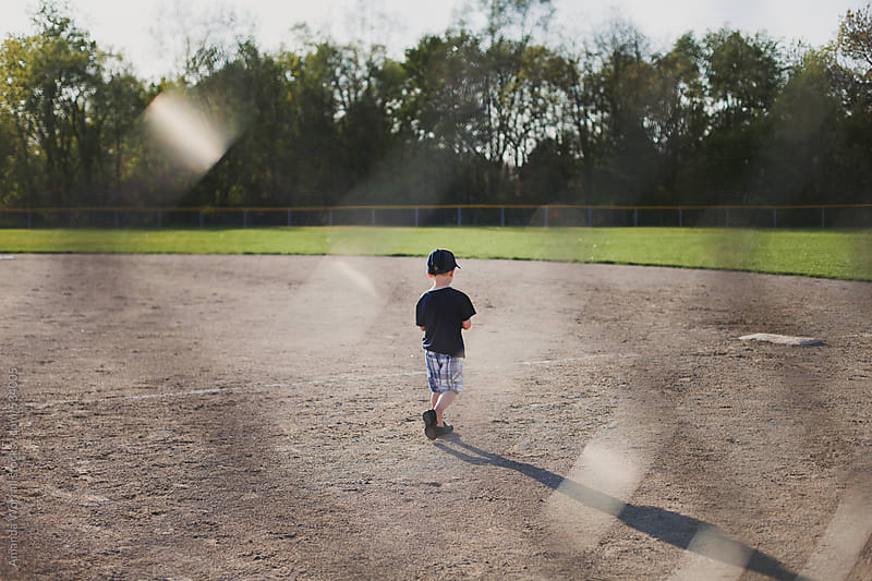 Young boy walks toward first base on baseball field by Amanda Worrall for Stocksy United