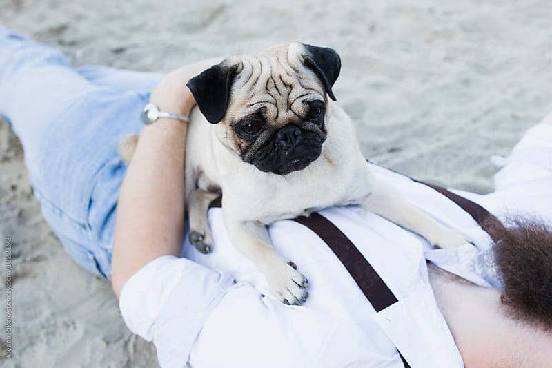 Young woman and a pug dog by Jovana Rikalo for Stocksy United