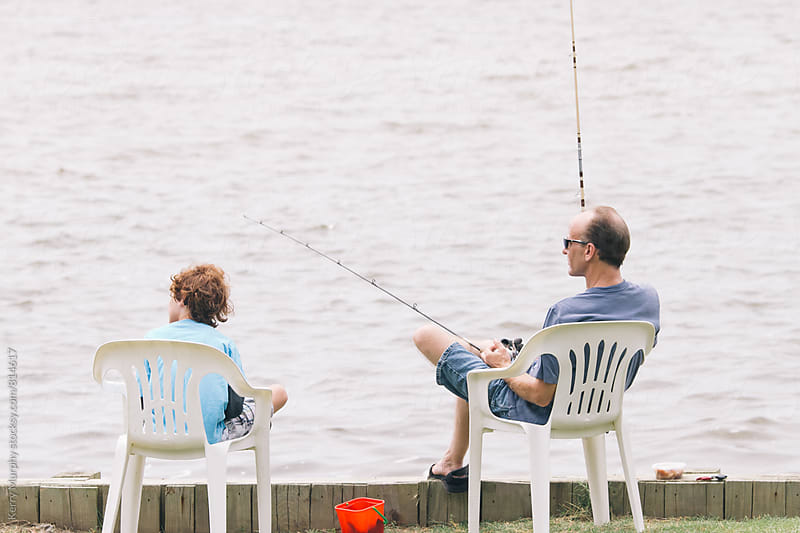 Father and young son fishing together by Kerry Murphy for Stocksy United