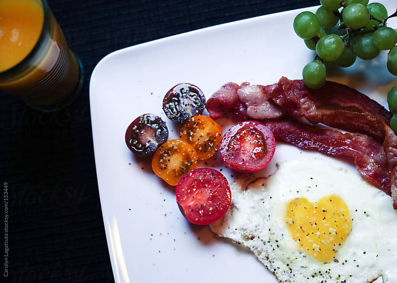 A breakfast consisting of an egg with a heart shaped yolk, juice, bacon and fruit by Carolyn Lagattuta for Stocksy United