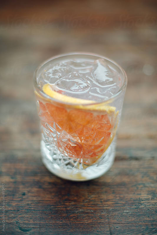 Grapefruit Gin & Tonic in Crystal Glass on Rustic Table by Hung Quach for Stocksy United