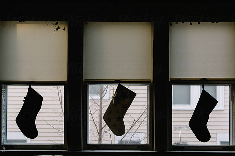 Three stockings hanging in a window by Gabriel (Gabi) Bucataru for Stocksy United