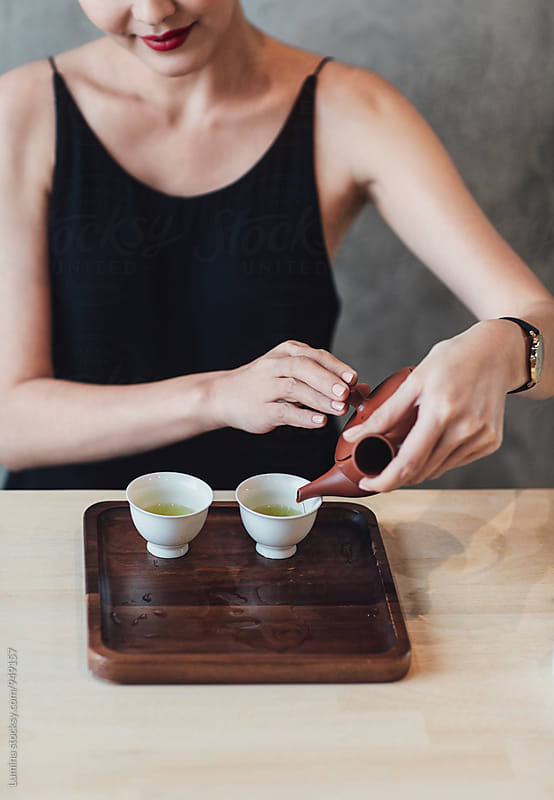 Woman Sitting and Pouring Herself some Tea.  by Lumina for Stocksy United