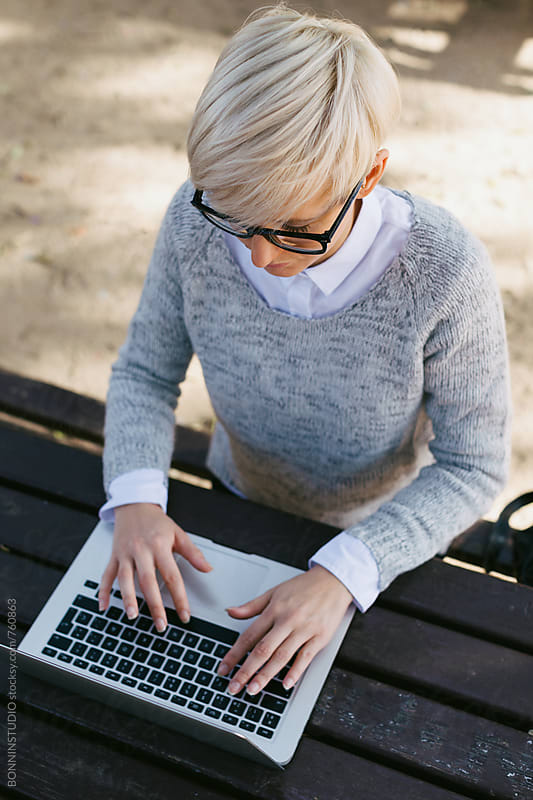 Overhead of a woman typing on her laptop sitting in the park. by BONNINSTUDIO for Stocksy United